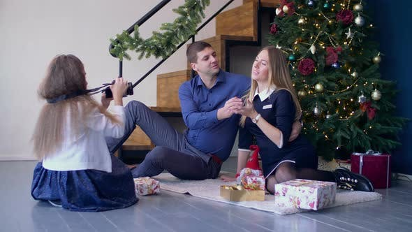 Thumbnail for Girl Taking Pictures of Her Happy Parents at Xmas
