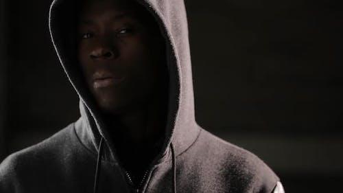 Hooligan Man Under Hood in Darkness