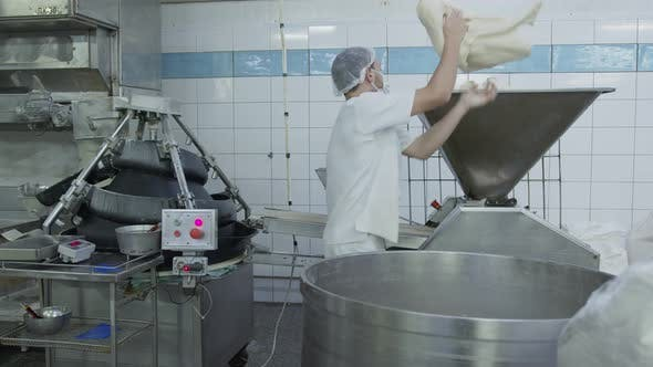 Bakery Production Line. A Bakery Worker Feeds the Dough Into an Automated Automatic Dough Feeder
