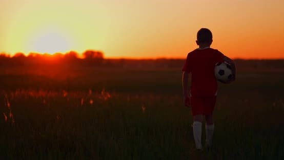 Thumbnail for The Camera Follows the Boy Walking Across the Field at Sunset with a Soccer Ball.