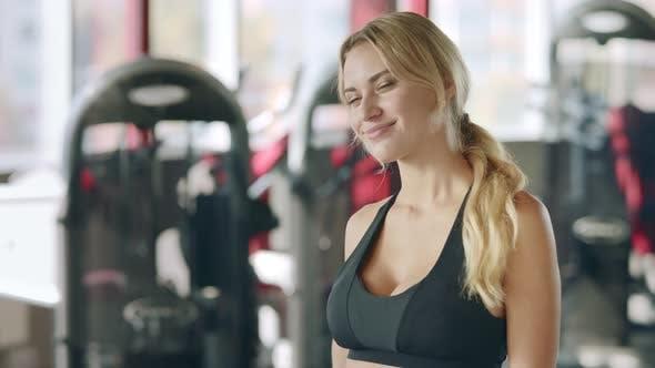Thumbnail for Fitness Frau zeigt Daumen nach oben und zwinkende Augen auf Sport Club Hintergrund