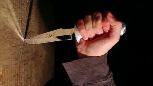 Mannes Hand klebt scharfe Jagdmesser in einer Holzwand