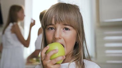 Girl is Eating a Big Green Apple