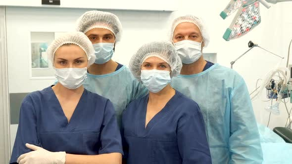 Thumbnail for Two Surgeons and Two Nurses Pose at the Surgery Room