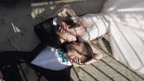 Thumbnail for Newlyweds. Caucasian Groom with Bride Lie on the Ground Next To Each Other