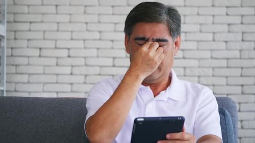 Senior man is suffering from eye strain due to his long-time looking at the digital tablet.
