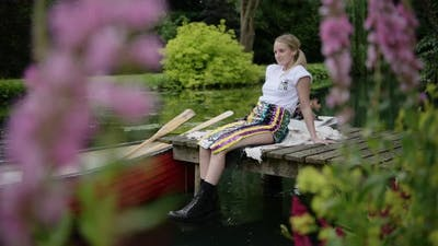 A Beautiful Woman Sitting On The Wooden Jetty By The Lake With A Boat Floating - full shot