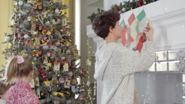 Thumbnail for Woman Decorating Fireplace for Christmas with Help of Kids