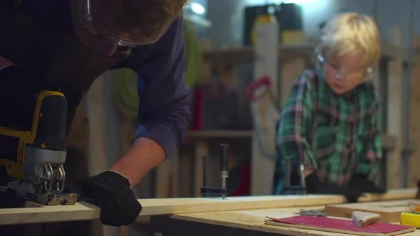 Thumbnail for The Boy Helps Dad To Cut a Board. Sliding