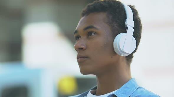 Upset Afro-American teen boy in headphones listening to music