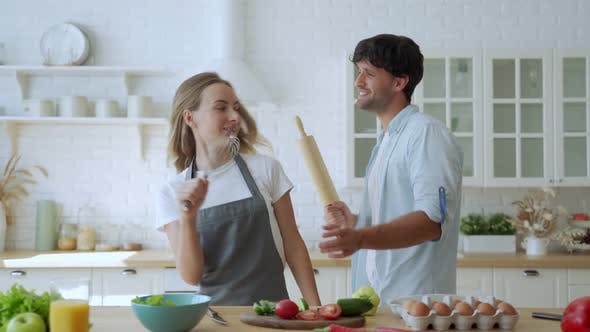 Thumbnail for Young Couple Laughing Holding Kitchenware Singing Song Together Dancing To Music Enjoying Cooking in