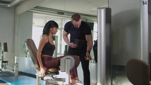 Thumbnail for Fitness Trainer Helping Woman To Exercise at Gym