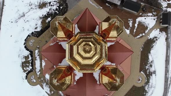 Aerial Top View on Ukrainian Church with Golden Domes in Carpathian Village in Winter