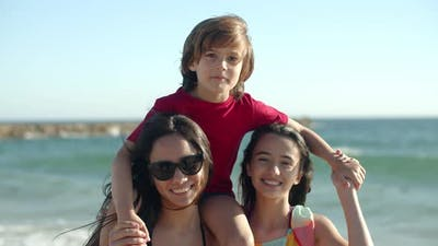 Happy Sisters Standing on Beach and Holding Brother on Neck