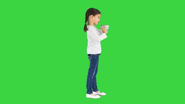 Excited Little Girl Play Videogame Holding Joystick in Her Hands on a Green Screen Chroma Key