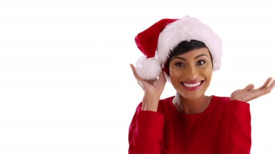 Thumbnail for Cheerful young woman modeling Santa Claus hat, smiling and laughing in studio