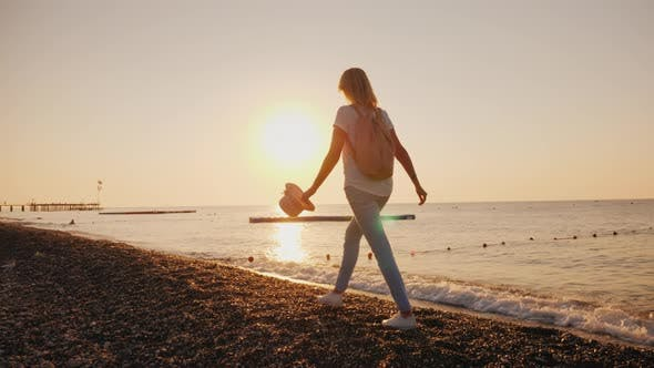 Cover Image for A Happy Woman Walks Carefree Along the Surf Line, the Sun Rises Over the Sea. Holiday and Vacation