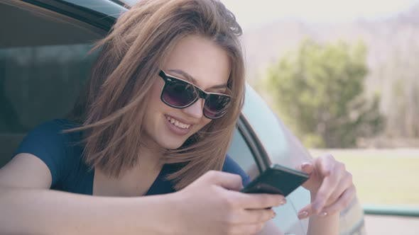 Thumbnail for Beautiful Lady Scrolls Social Media on Cellphone in Car