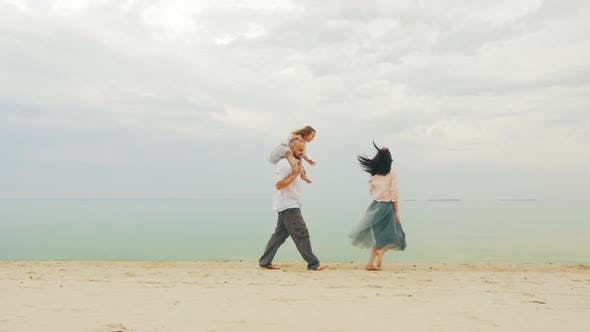 Thumbnail for Happy Family of Three People Running on the Beach