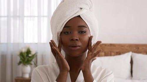 Glamorous Black Lady Applying Moisturizing Cream Touching Face In Bedroom