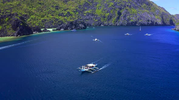Cover Image for Aerial Drone View of White Traditional Filipino Boat Floating on Top of Clear Blue Water Surface