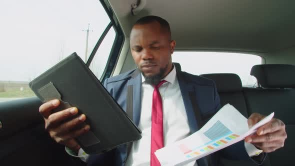 Black Businessman Working with Tablet Pc in Backseat of Car