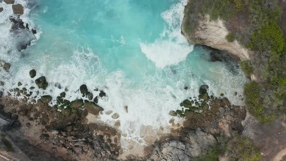 Thumbnail for Overhead view of waves breaking inside a small rocky bay