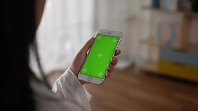 Closeup of hand woman holding smartphone with green screen