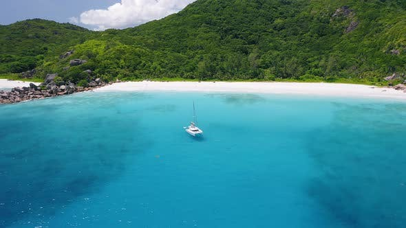 Thumbnail for Aerial View Footage of Luxury Catamaran Yacht Moored in Clear Turquoise Blue Ocean Water of Petite