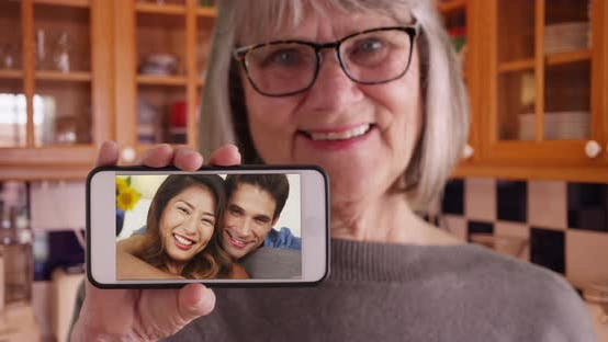 Thumbnail for Old lady holding phone to camera while videochatting with son and his girlfriend