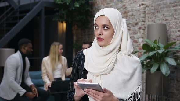 Thumbnail for Muslim Businesswoman in Hijab Typing on i-pad and Standing in the Modern Office