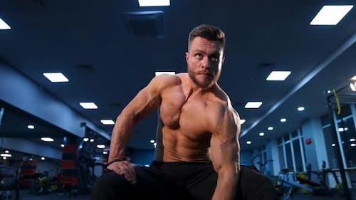 Athletischer Mann trainiert mit Hantel. Leistungsstarker Bodybuilder macht die Übungen mit Hanteln