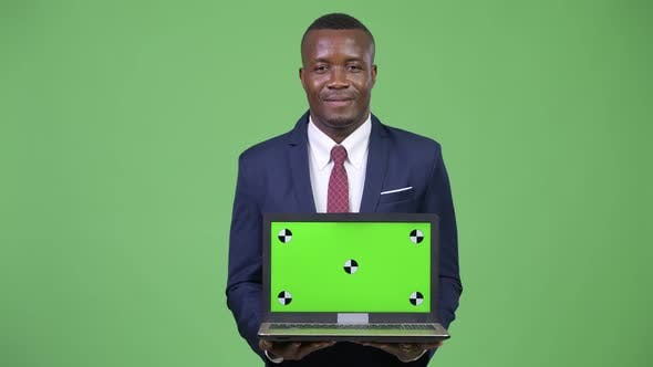 Thumbnail for Young Happy African Businessman Showing Laptop