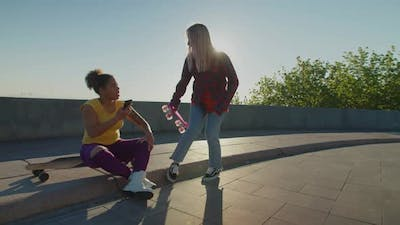 Lovely Multiracial Females with Skateboards Meeting for Ride in Morning