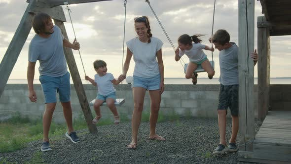 Thumbnail for Happy Family Rolls Young Children on a Swing Outdoors at Sunset