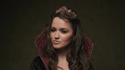 Female in Cloak and Crown. Portrait of Vampiress Looking at Camera. , UHD