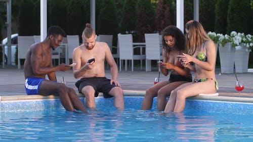 Freudige Freunde mit Handys sitzen auf Pool Seite
