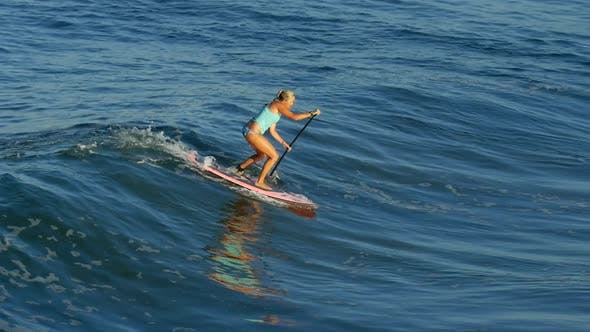 A young woman SUP surfing in a bikini on a stand-up paddleboard surfboard.