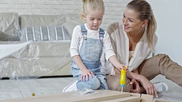 Thumbnail for Girl Assembling Furniture with Toy Screwdriver