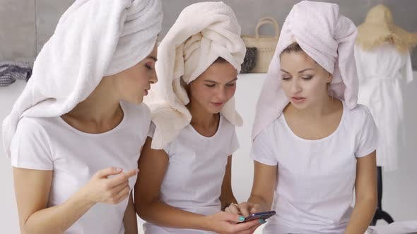 Cover Image for Three Positive Girlfriends in White T-shirts with Towels on Heads Spending Time Together at Home