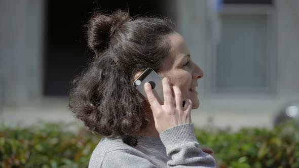 Thumbnail for Happy Brunette Woman Talking on Smartphone Outdoor
