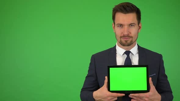 Thumbnail for A Young Businessman Shows a Tablet with Green Screen To the Camera and Smiles - Green Screen Studio