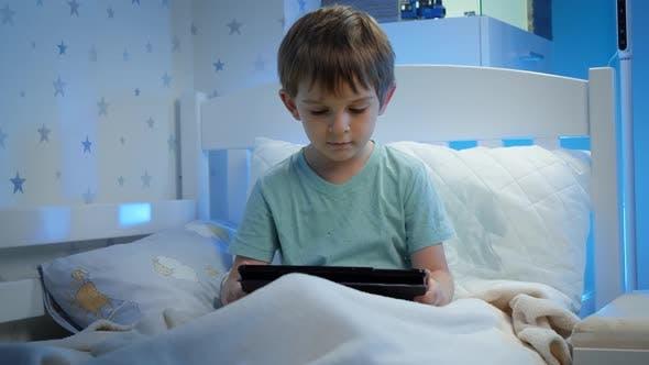 Porträt eines kleinen Kleinkindes, der nachts im Bett sitzt und Video auf einem Tablet-Computer ansieht