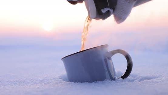 Thumbnail for An einem kalten Wintertag Tee aus einer Thermosflasche in eine Tasse gießen
