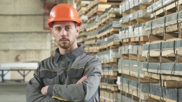 Thumbnail for Portrait of a Handsome Serious Metalworker Posing at the Factory Storage