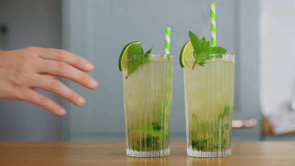 Hand Taking Glass of Mojito Cocktail From Table