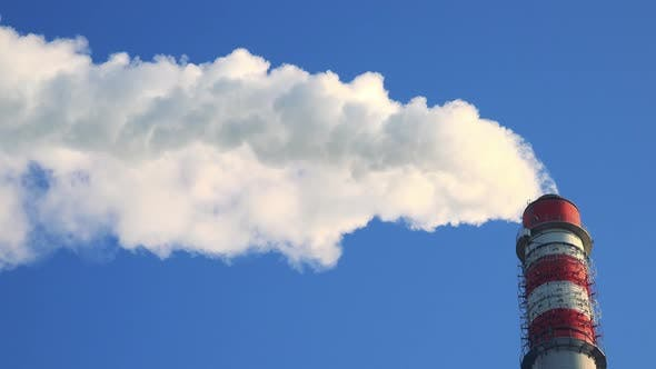 Thumbnail for A Smokestack Emits Smoke - the Clear Blue Sky in the Background