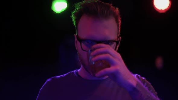 Thumbnail for Portrait of Handsome Bearded Guy in Glasses Drinking Alcoholic Drink From a Glass Standing