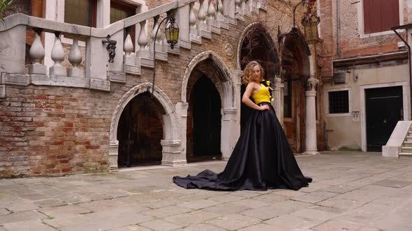 Lady in Evening Dress Holds Hand on Hip and Poses for Camera