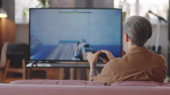 Man Playing Shooter Video Game on TV at Home